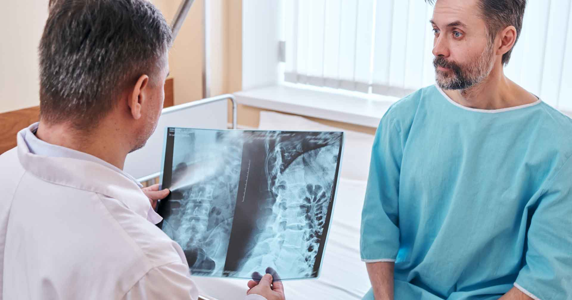Doctor is checking the spinal disk of a patient and examining the xray of the spinal cord